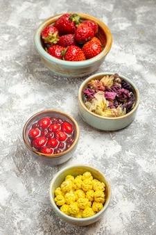 흰색 표면 베리 사탕 과일에 사탕과 전면보기 신선한 빨간 딸기