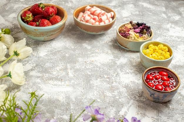 正面図白い表面のフルーツゼリーの花にキャンディーと新鮮な赤いイチゴ