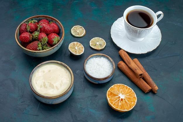 Vista frontale di fragole rosse fresche con cannella e tazza di tè sulla scrivania blu