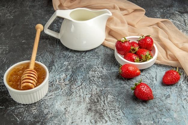 Вид спереди свежей красной клубники с медом на темно-светлой поверхности красных ягод