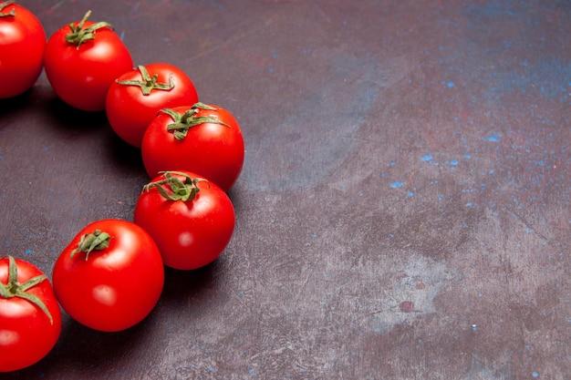 Vista frontale pomodori rossi freschi cerchiati nello spazio scuro on