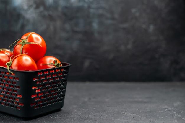 暗い背景のサラダ熟した色の食事の写真の空きスペースにバスケットの中の新鮮な赤いトマトの正面図