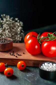 暗い背景に新鮮な赤いトマトの正面図