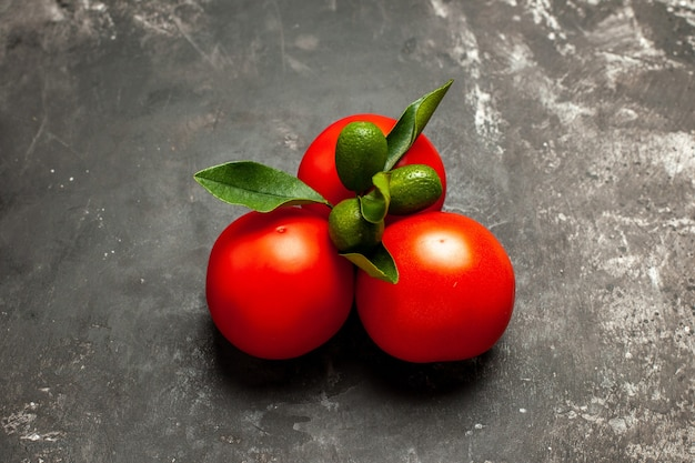 Вид спереди свежие красные помидоры на темной поверхности спелых красных овощей