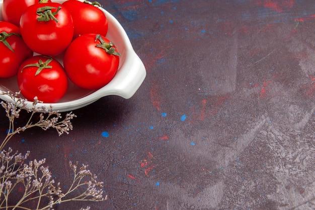 暗いスペースのプレート内の新鮮な赤いトマトの熟した野菜の正面図