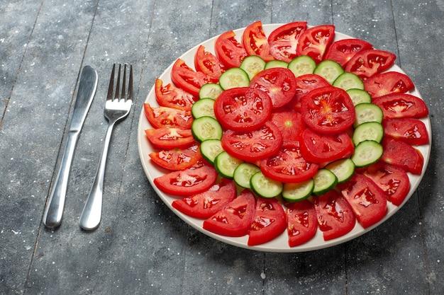 素朴な灰色の机の上に新鮮な赤いトマトスライスした新鮮なサラダの正面図