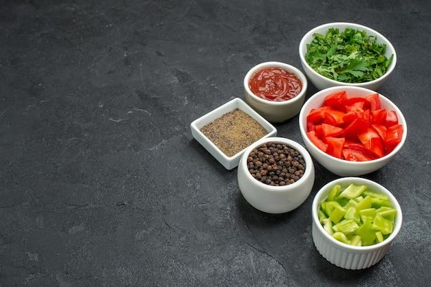 Вид спереди свежие красные помидоры, нарезанные овощи с зеленью на темном столе, спелый салат, здоровая еда