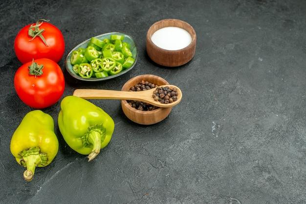 Vista frontale pomodori rossi freschi con peperoni su backgruond scuro pasto maturo insalata dieta alimentare salute