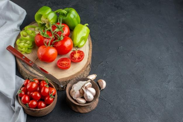 Вид спереди свежие красные помидоры с чесноком и зеленым болгарским перцем на темной поверхности