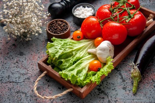 Vista frontale pomodori rossi freschi con aglio e insalata verde all'interno della tavola di legno su sfondo blu