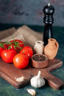 어두운 배경에 마늘과 전면보기 신선한 빨간 토마토