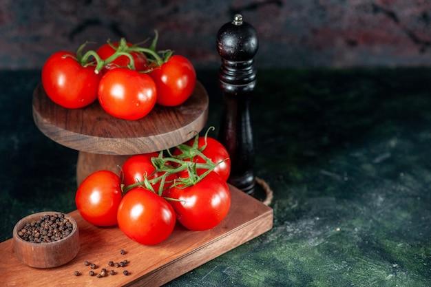 暗い背景にコショウと新鮮な赤いトマトの正面図