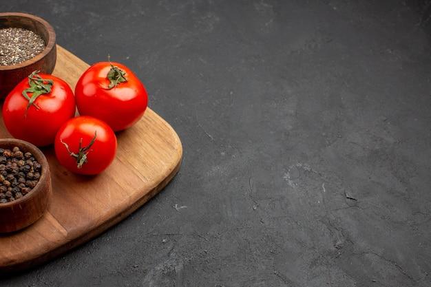 暗いスペースに調味料を入れた正面の新鮮な赤いトマト