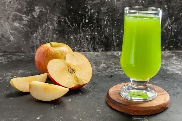 暗いまろやかなジュースの木の写真の色に青リンゴ ジュースと新鮮な熟したリンゴの正面図