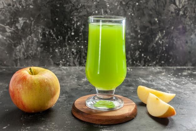 暗い机のまろやかなジュースの木の写真の色に青リンゴ ジュースと新鮮な熟したリンゴの正面図