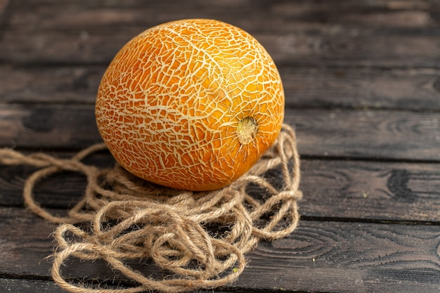 Front view fresh ripe melon whole orange ed with ropes on the brown rustic desk