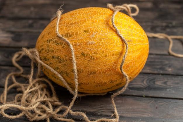 Вид спереди свежей спелой дыни целиком оранжевого цвета с веревками на коричневом деревенском фоне