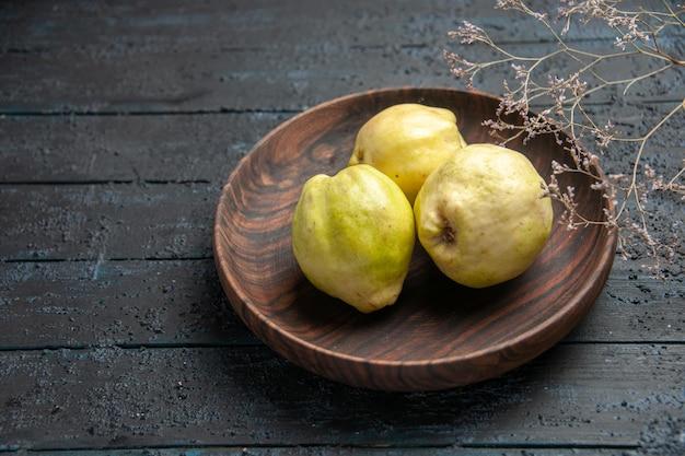 Vista frontale mele cotogne mature fresche frutti acidi all'interno del piatto su albero rustico blu scuro da scrivania frutta matura albero fresco