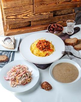 茶色のキノコのスープと茶色の机の上の調理されたパスタと一緒に正面の新鮮なサラダ
