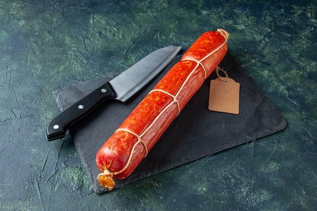 Вид спереди свежая колбаса с ножом на темно-синем мясном бургере, цветная еда для животных, сэндвич с хлебом