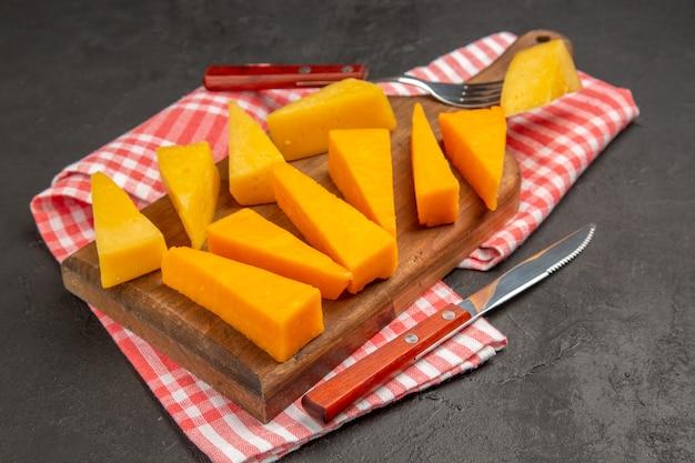 正面から見た新鮮なスライス チーズ、濃い灰色の食事の写真、朝食の cips カラー フード