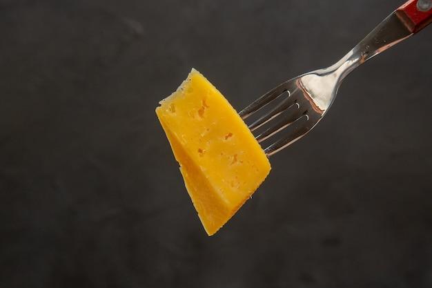 正面から見た新鮮なスライス チーズ フォークの暗い色のスナックの写真朝食のパリッとした食事