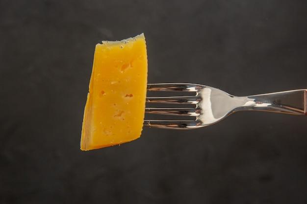 正面から見た新鮮なスライス チーズ フォーク ダーク スナック料理