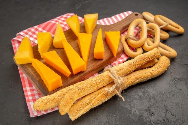 正面から見た新鮮なスライス チーズ、濃い灰色の食事の写真にパンとクラッカーが付いています。