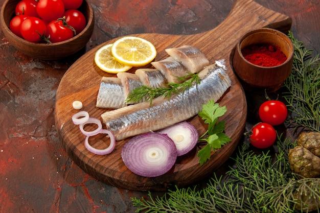Vista frontale pesce fresco affettato con pomodori freschi sullo spuntino di carne di insalata di foto a colori di pesce scuro