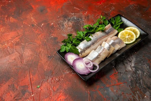 正面から見た新鮮なスライスされた魚と緑とタマネギの黒い鍋の中に暗いスナック肉の食事の魚介類の写真