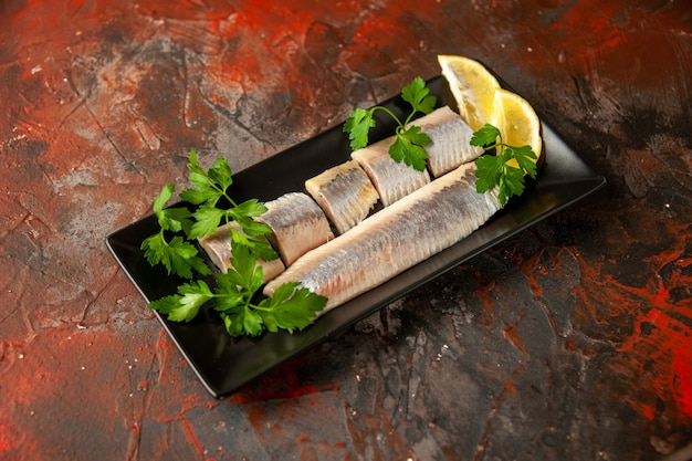 Front view fresh sliced fish with greens and lemon pieces inside black pan on dark snack meat food