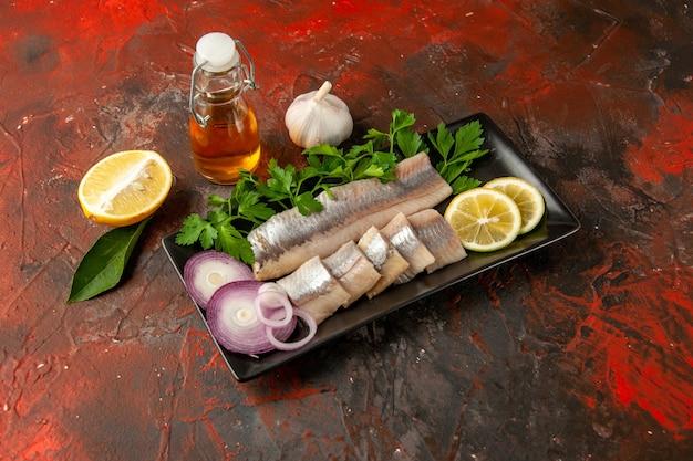 Vista frontale pesce fresco affettato con verdure e cipolla all'interno di una padella nera su foto scura snack farina di pesce colore