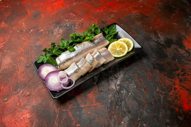 Vista frontale di pesce fresco a fette con verdure e cipolla all'interno di una padella nera su spuntino scuro a base di carne di pesce a base di pesce