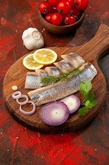 正面から見た新鮮なスライスした魚、タマネギの輪とトマト、黒っぽい肉のスナックの食事の色の魚介類