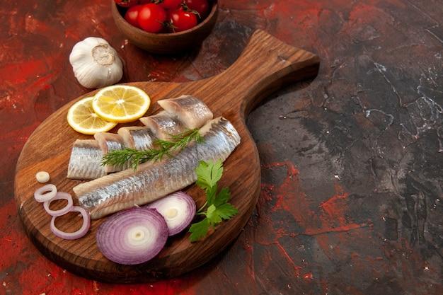 暗いスナックの食事の色の肉シーフードにオニオン リングとトマトを添えた新鮮なスライスした魚を正面から見た図