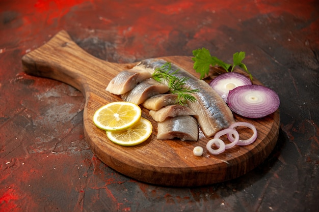 Front view fresh sliced fish with onion rings and lemon on dark meal meat seafood snack color photo