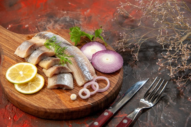 Front view fresh sliced fish with onion rings and lemon on dark snack meal meat seafood color photo
