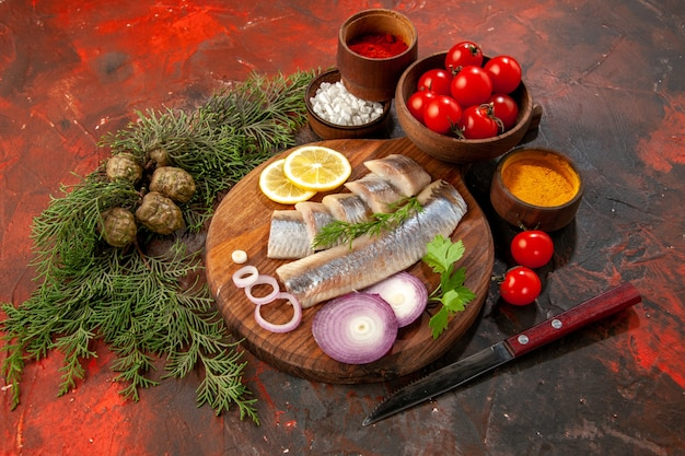 暗いシーフード カラー写真スナック ミート サラダに調味料トマトとチーズと新鮮なスライスした魚の正面図