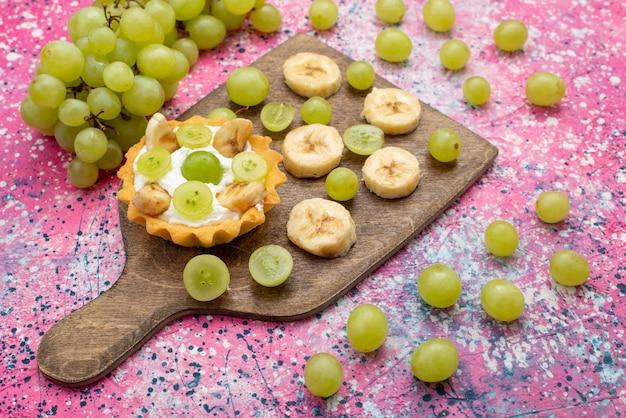 Вид спереди свежие нарезанные фрукты, виноград и бананы с кремовым пирогом на фиолетовой поверхности, фруктовый мягкий цвет, витамин