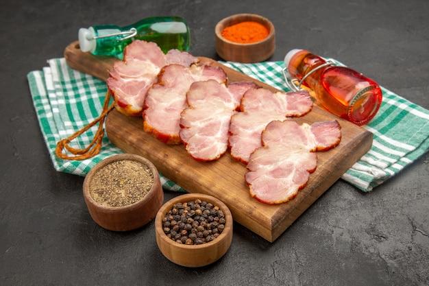 Prosciutto affettato fresco di vista frontale con i condimenti sul colore della foto del maiale crudo della carne grigia dell'alimento