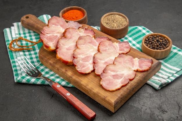 正面から見た新鮮なスライス ハムに調味料を付けた濃い灰色の食品の肉の生写真