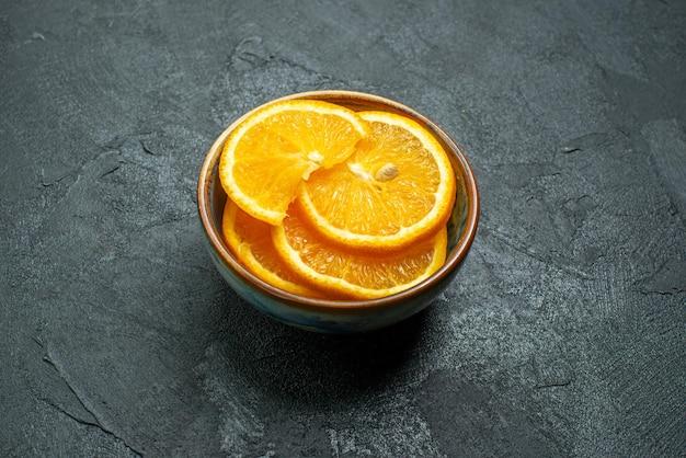 暗い表面の柑橘類のエキゾチックなトロピカルフルーツジュースのプレート内の新鮮なスライスしたオレンジの正面図