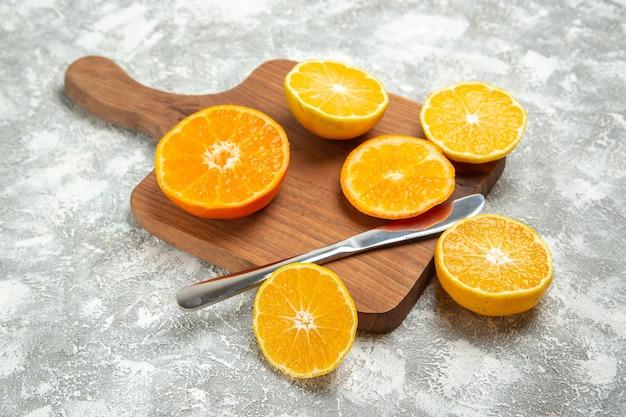 Вид спереди свежие нарезанные апельсины спелые цитрусы на светлом белом фоне спелые фрукты экзотические свежие тропические
