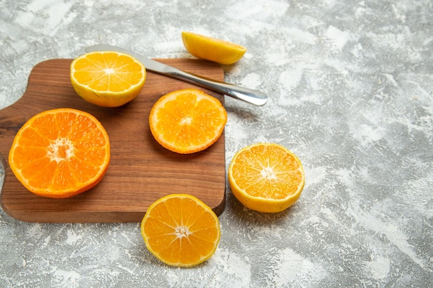 Вид спереди свежие нарезанные апельсины спелые цитрусы на белом фоне спелые фрукты экзотические свежие тропические