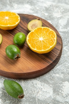 Вид спереди свежие нарезанные апельсины с фейхоа на белом фоне спелые фрукты экзотические тропические свежие