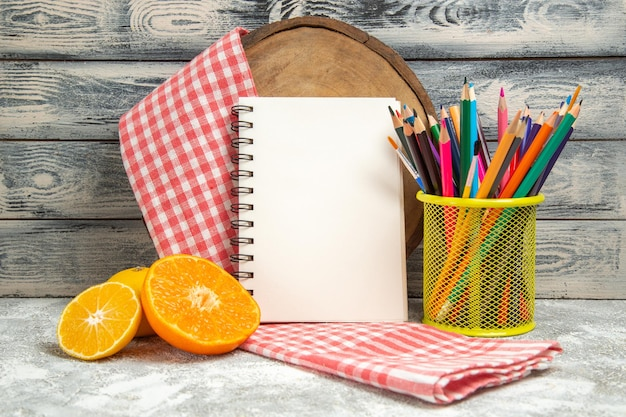 Front view fresh sliced oranges with notepad and pencil on grey background fruit citrus copybook color