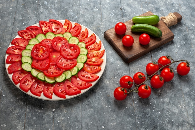 Front view fresh sliced tomatoes elegantly designed salad on grey rustic space