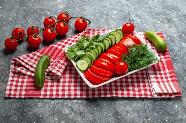 Vista frontale pomodori freschi affettati insalata dal design elegante sullo spazio grigio