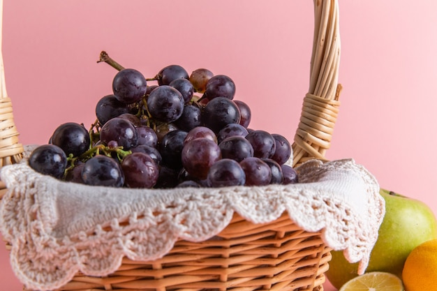 Front view of fresh sour grapes inside basket on pink wall