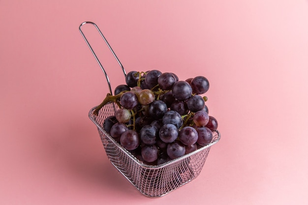 Front view of fresh sour grapes inside fryer on the pink wall